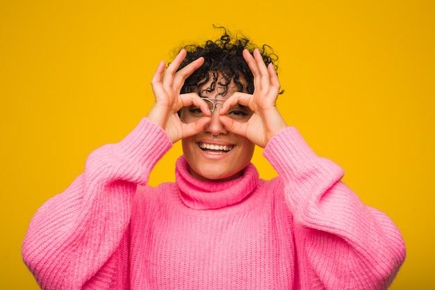 Молодая афро-американская женщина нося розовый свитер показывая одобренный знак над глазами
