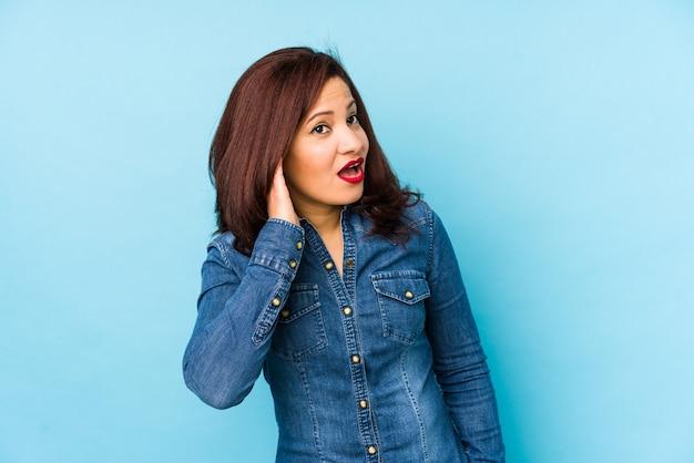 Женщина среднего возраста латинская изолированная на голубой стене пробуя слушать сплетню.