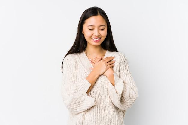 Молодая китайская женщина изолировала смеяться над держащ руки на сердце, концепции счастья.