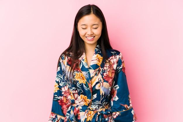 Молодая китайская женщина в пижаме кимоно изолировала смех и закрывает глаза, чувствует себя расслабленной и счастливой.