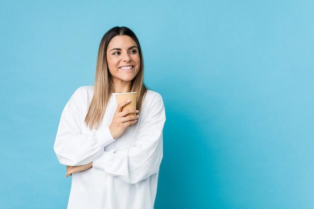 組んだ腕に自信を持って笑顔のテイクアウトコーヒーを保持している若い白人女性。