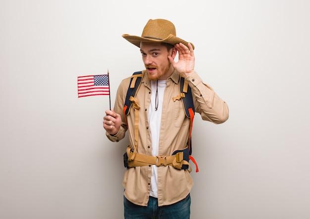 若い赤毛の探検家の男は、ゴシップを聞いてみてください。アメリカ合衆国のフラグを保持しています。
