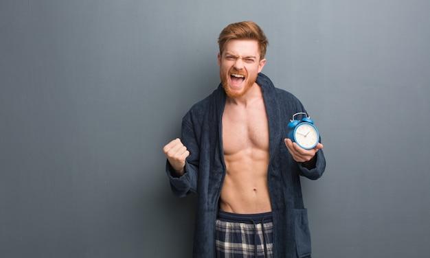 Рыжий молодой человек в пижаме удивлен и шокирован. он держит будильник.