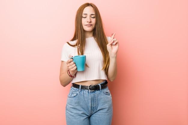 Молодая женщина держит чашку скрещивания пальцев для удачи