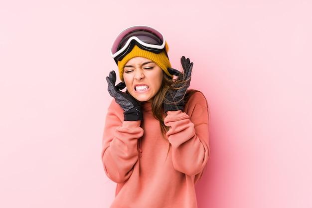 Молодая женщина нося одежду лыжи изолировала покрывать уши руками.