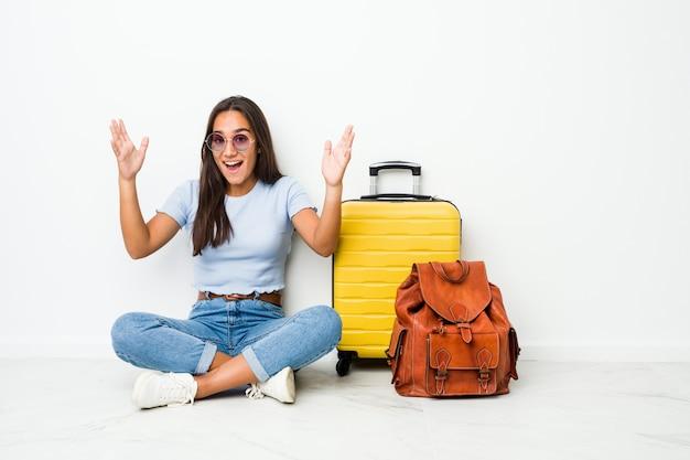 若い混合レースインドの女性は、楽しい驚き、興奮して手を上げる旅行に行く準備ができています。