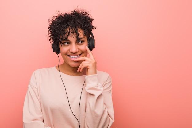 Молодая афро-американская женщина слушая к музыке ослабила думать о что-то смотря космос экземпляра.