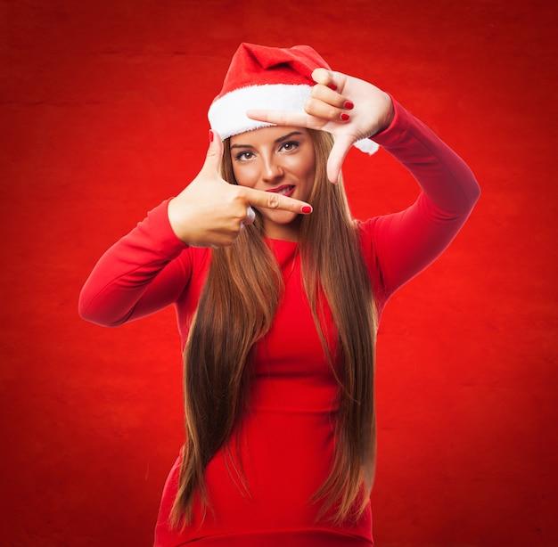 赤い背景に彼女の指を使ってフレームを作る女