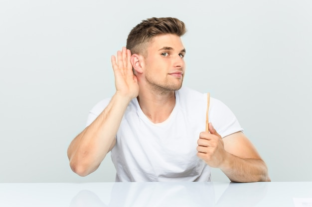ゴシップを聴こうとして歯ブラシを保持している若い男。