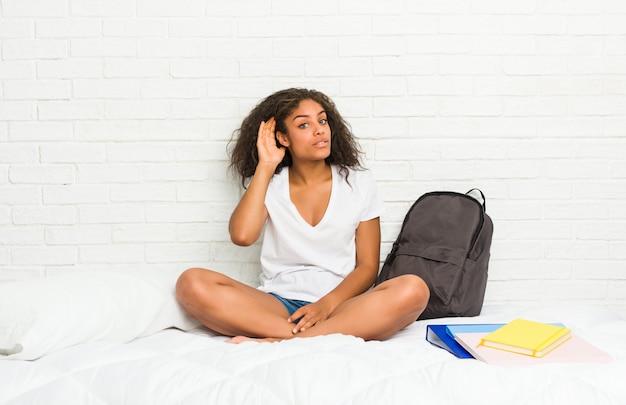 ゴシップを聴こうとしてベッドの上の若いアフリカ系アメリカ人学生女性。