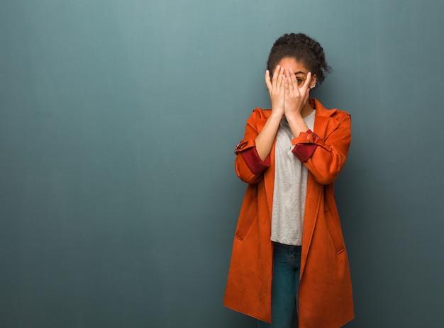 青い目を持つ若い黒人アフリカ系アメリカ人の女の子は心配と怖い感じています。