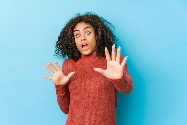 差し迫った危険のためにショックを受けている若いアフリカ系アメリカ人の巻き毛の女性