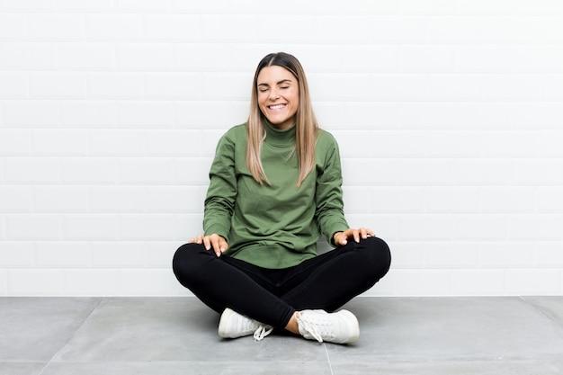 Молодая женщина кавказской, сидя на полу, смеется и закрывает глаза, чувствует себя расслабленным и счастливым.