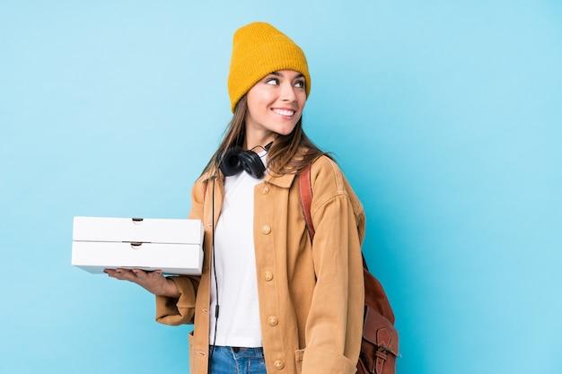 Молодая женщина кавказской холдинг пиццы смотрит в сторону, улыбаясь, веселый и приятный.