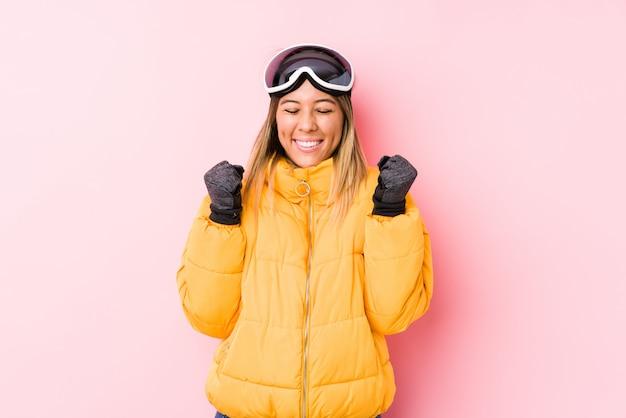 幸せと成功を感じて、拳を上げるピンクの壁にスキー服を着た若い白人女性。勝利のコンセプト。