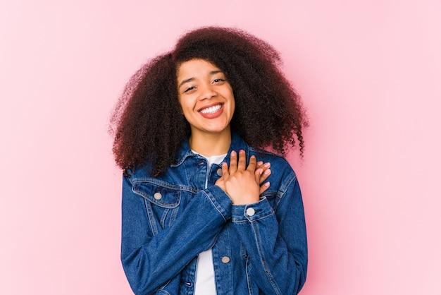 Молодая афроамериканская женщина имеет дружелюбное выражение, прижимая ладонь к груди. концепция любви