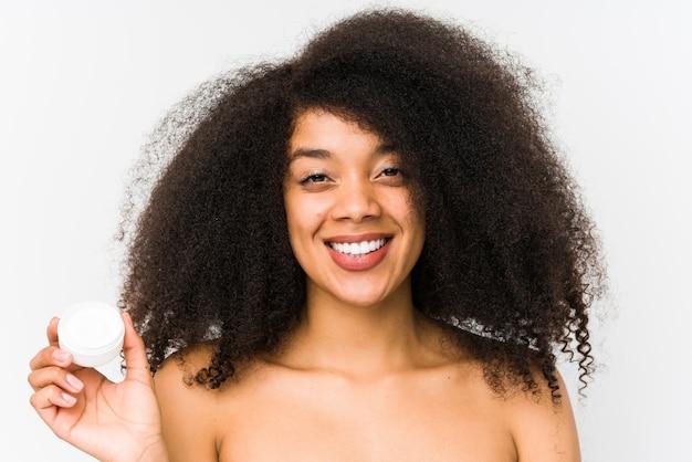 保湿剤を保持している若いアフロ女性は幸せ、笑顔、陽気な分離しました。
