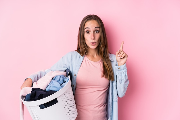 いくつかの素晴らしいアイデア、創造性の概念を持つ分離された汚れた服を拾う若い白人女性。