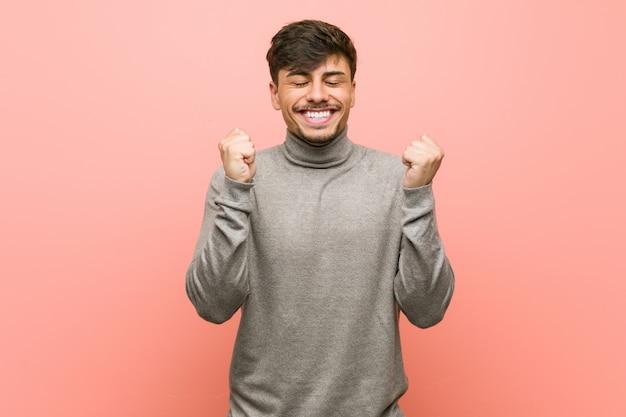 Молодой умный студент человек поднимая кулак, чувствуя себя счастливым и успешным. концепция победы.