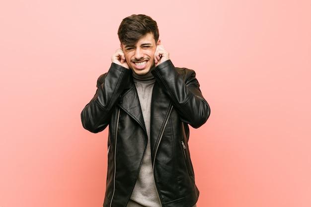 Молодой латиноамериканский человек, носящий кожаную куртку, покрывающую уши руками.