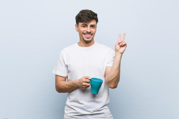 Молодой испанец человек держа чашку показывая номер два с пальцами.