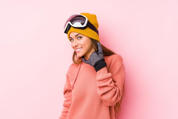 指で携帯電話の通話ジェスチャーを示す分離されたスキー服を着た若い白人女性。