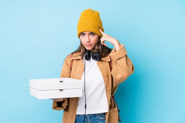 Молодая кавказская женщина держа пиццы изолировала указывающ висок с пальцем, думая, сфокусированным на задаче.