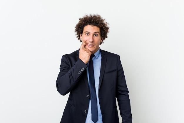 爪をかむ白い背景に対して若いビジネス中の男、神経質で非常に心配しています。