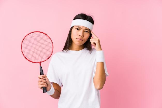 Молодая женщина, играя в бадминтон в розовый указывая храм с пальцем, думая, сосредоточены на задаче.
