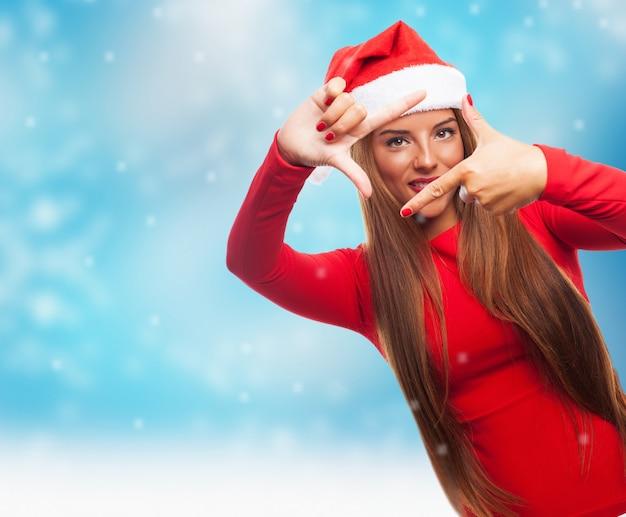 雪が降っている間女性は彼女の指でフレームを作ります