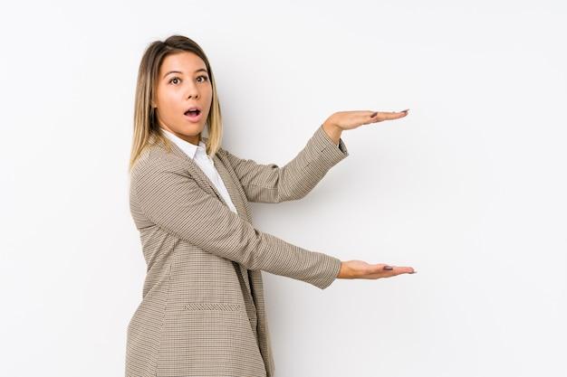 Молодой бизнес женщина шокирован и удивлен, держа копию пространства между руками.