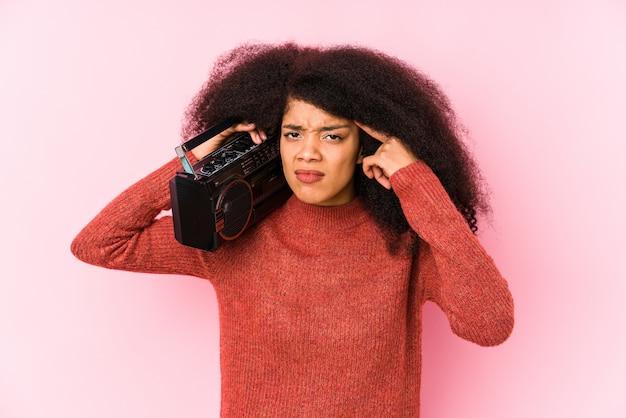 人差し指で失望のジェスチャーを示すカセットを保持している若い女性。