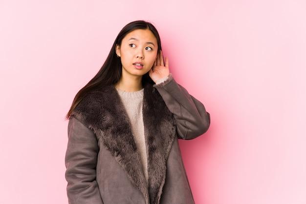 ゴシップを聴こうとして分離されたコートを着ている若い中国人女性。