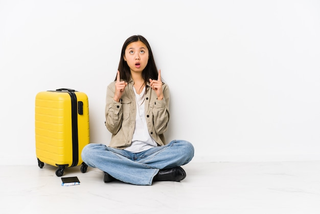 搭乗券を持って座っている若い中国人旅行者の女性は、開いた口で逆さを指しています。