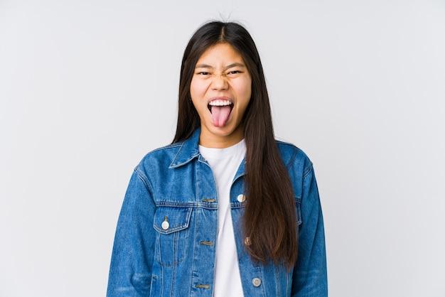 舌を突き出して面白いとフレンドリーな若いアジア女性。