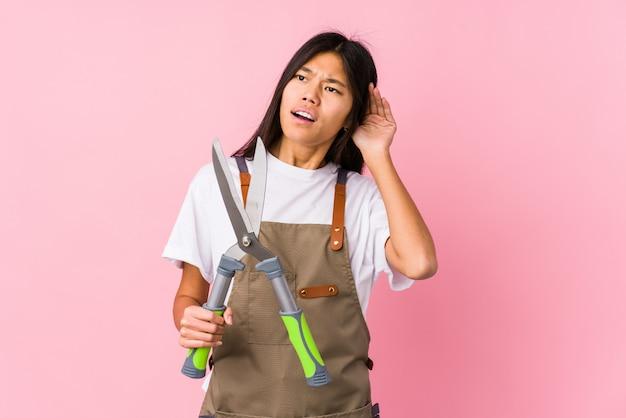 Молодая китайская женщина садовника держащ ножницы изолировала пробовать слушать сплетню.