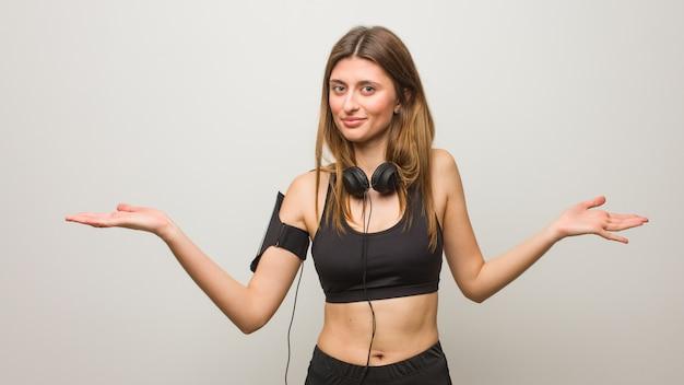 Молодая фитнес русская женщина смущена и сомнительна