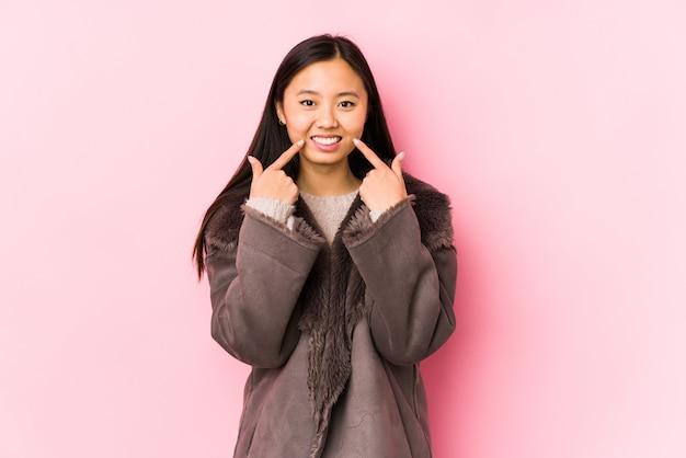 コートを着た若い女性の笑顔、口に指を指しています。