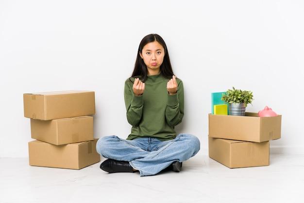 彼女はお金がないことを示す新しい家に移動する若い女性。