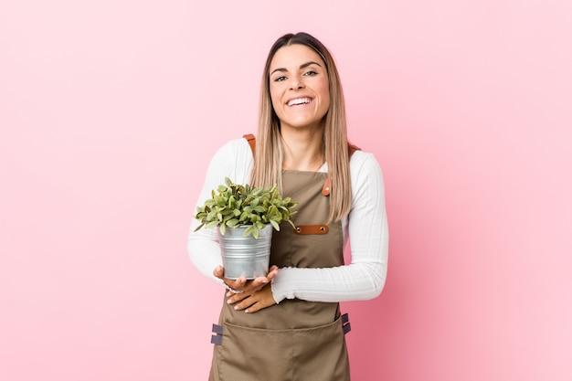 笑いと楽しい植物を保持している若い庭師女性。