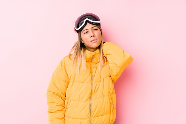 座りがちな生活のために首の痛みに苦しんでいるピンクの背景でスキー服を着ている若い白人女性。