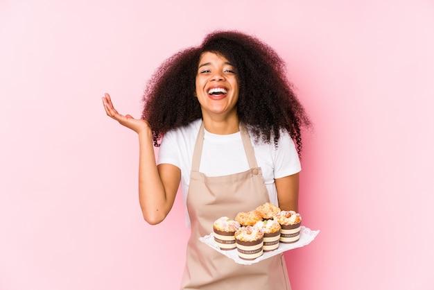 分離されたカップケーキを保持している若いアフロペストリーメーカー女性