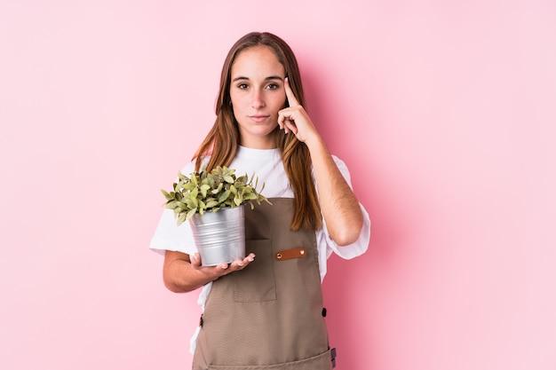 若い庭師白人女性が指で指差し、思考、タスクに焦点を当てて分離しました。