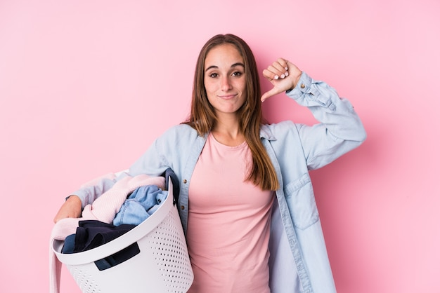 嫌なジェスチャー、親指ダウンを示す分離された汚れた服を拾う若い白人女性。不一致の概念。