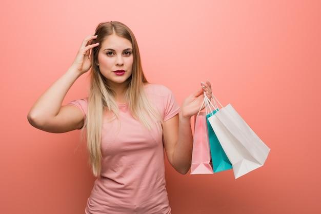 Молодая красивая русская девушка переживает и перегружена она держит сумки для покупок.
