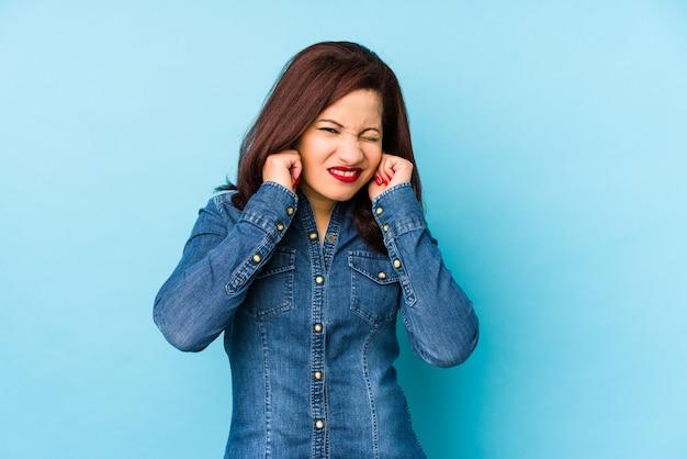 Среднего возраста латинской женщина, изолированных на синем фоне, охватывающих уши руками.