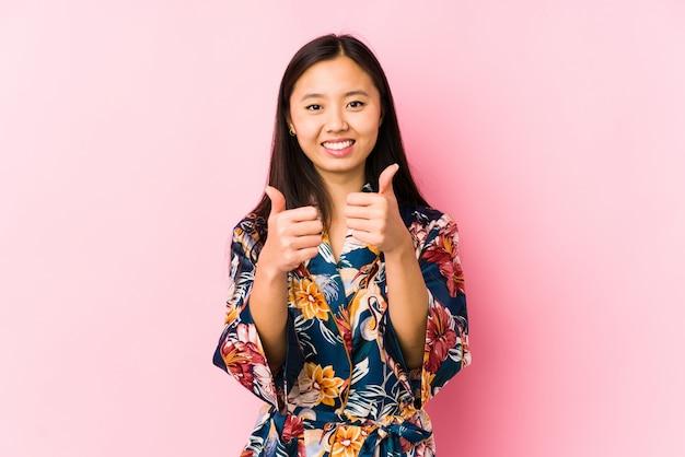 Молодая китайская женщина нося пижаму кимоно изолированную с большими пальцами руки поднимает, веселит о что-то, концепции поддержки и уважения.