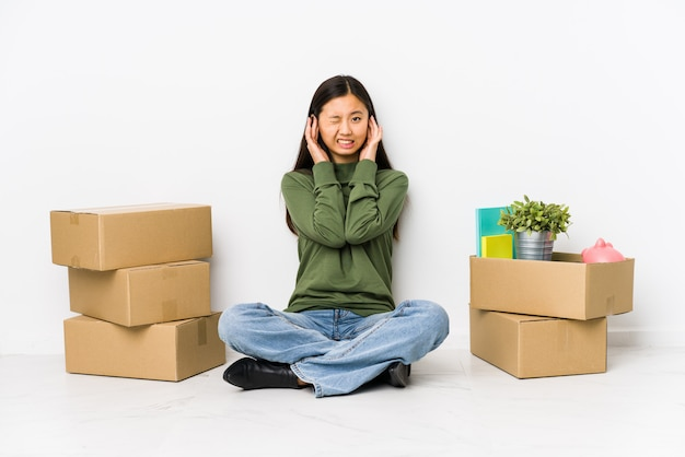 Молодая китайская женщина двигая к новому дому покрывая уши руками.
