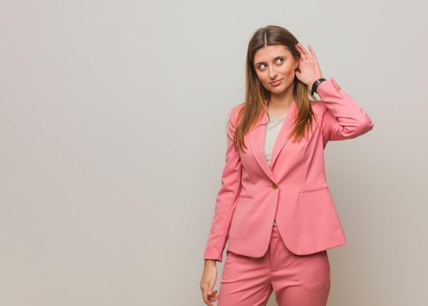 Молодая деловая русская девушка пытается слушать сплетни