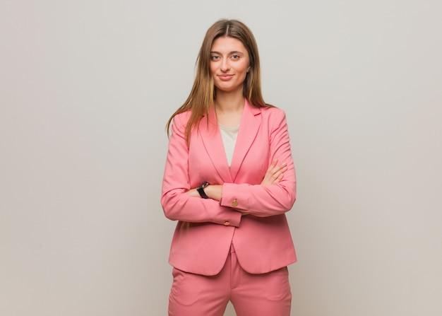 若いビジネスロシアの女の子の腕を交差、笑みを浮かべて、リラックス